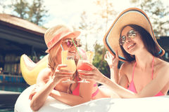Amigos de las mujeres jovenes en la diversión de la piscina Imagen de archivo