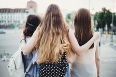Amigos de las mujeres jovenes que abrazan mirando la opinión de la ciudad Imagen de archivo libre de regalías
