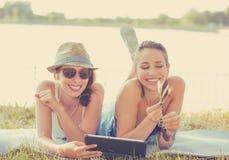 Amigos de las mujeres jovenes que ríen medios blogs sociales de observación en el ordenador del cojín foto de archivo libre de regalías