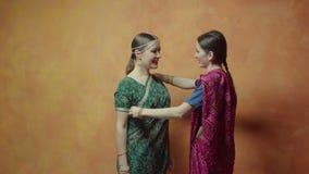 Amigos de las mujeres que caben la sari hindú y que comunican metrajes