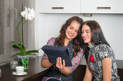 Amigos de las mujeres que charlan en casa y que usan el ordenador portátil para mirar nuevo p Imagenes de archivo