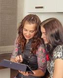 Amigos de las mujeres que charlan en casa y que usan el ordenador portátil para mirar nuevo p Foto de archivo libre de regalías