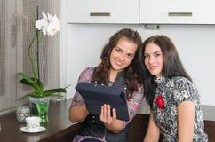 Amigos de las mujeres que charlan en casa y que usan el ordenador portátil para mirar nuevo p Imagen de archivo libre de regalías