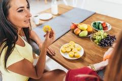 Amigos de las mujeres que comen las frutas y verduras en cocina Nutrición sana Comida con pocas calorías fotografía de archivo libre de regalías