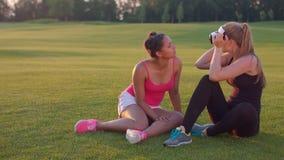 Amigos de las mujeres que se divierten con las auriculares de la realidad virtual al aire libre metrajes