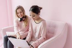 Amigos de las mujeres que se sientan en sala de estar junto Imagenes de archivo
