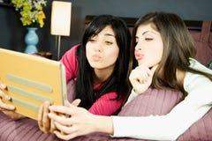Amigos de las mujeres que toman el selfie en la cama divertida Fotos de archivo