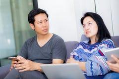 Amigos de las personas del asiático dos en línea con los dispositivos múltiples y hablar en el sofá Imagen de archivo libre de regalías