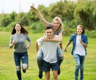 Amigos de los adolescentes que corren en prado Fotos de archivo