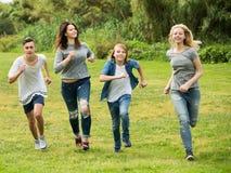 Amigos de los adolescentes que corren en prado Imagen de archivo libre de regalías