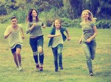 Amigos de los adolescentes que corren en prado Imagen de archivo