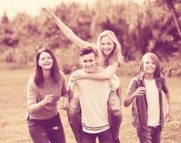 Amigos de los adolescentes que corren en prado Fotografía de archivo