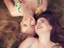 Amigos de los adolescentes que mienten en una hierba que ríe en un parque Imagenes de archivo