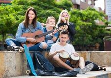 Amigos de los adolescentes que tocan los instrumentos musicales Imagen de archivo