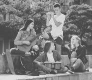 Amigos de los adolescentes que tocan los instrumentos musicales Imagenes de archivo