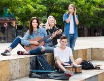 Amigos de los adolescentes que tocan los instrumentos musicales Fotografía de archivo