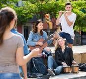 Amigos de los adolescentes que tocan los instrumentos musicales Foto de archivo