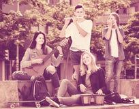 Amigos de los adolescentes que tocan los instrumentos musicales Fotos de archivo