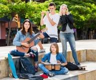 Amigos de los adolescentes que tocan los instrumentos musicales Fotos de archivo libres de regalías