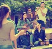 Amigos de los adolescentes que tocan los instrumentos musicales Imágenes de archivo libres de regalías