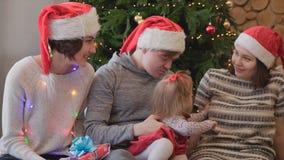 Amigos de los adultos que juegan con una niña cerca del árbol de navidad Reuniones amistosas cerca del árbol de navidad con fotografía de archivo libre de regalías