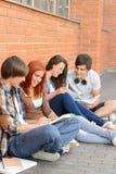 Amigos de los estudiantes que se sientan en la tierra fuera del campus Foto de archivo