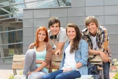 Amigos de los estudiantes que sientan el banco fuera del campus imagenes de archivo
