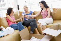 Amigos de menina que brindam o champanhe na HOME nova Fotos de Stock Royalty Free