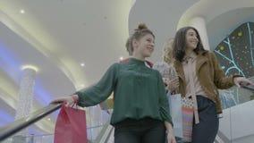 Amigos de meninas do estudante na alameda usando escadas rolantes e falando sobre tipos e compra - vídeos de arquivo
