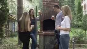 Amigos de Millennials que aumentam vidros de cerveja para um brinde que tem o divertimento no partido exterior perto da grade no  filme