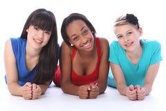 Amigos de muchacha blancos y asiáticos negros que mienten en suelo Imagen de archivo
