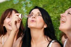 Amigos de muchacha con las burbujas de jabón Imagen de archivo libre de regalías