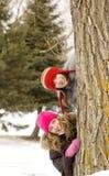Amigos de muchacha detrás de un árbol Foto de archivo libre de regalías