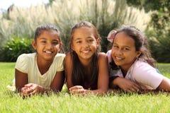 Amigos de muchacha felices de la escuela que mienten en hierba junto Foto de archivo