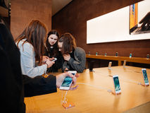 Amigos de muchachas del adolescente que prueban el último iphone de Apple Store Imágenes de archivo libres de regalías