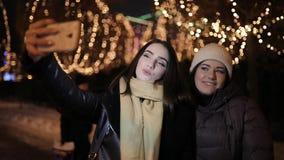 Amigos de muchachas que hacen la foto del selfie en el callejón de la noche adornado por la guirnalda metrajes