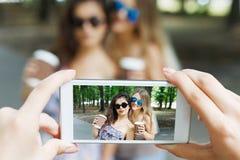 Amigos de muchachas que toman las fotos con smartphone al aire libre Fotos de archivo libres de regalías