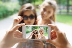Amigos de muchachas que toman las fotos con smartphone al aire libre Foto de archivo