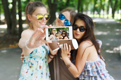 Amigos de muchachas que toman las fotos con smartphone al aire libre Imagenes de archivo