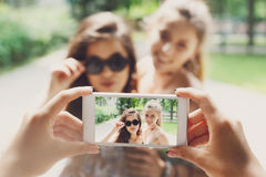 Amigos de muchachas que toman las fotos con smartphone al aire libre Imagen de archivo libre de regalías