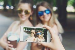 Amigos de muchachas que toman las fotos con smartphone al aire libre Imagen de archivo