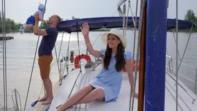 Amigos de ondulação da mão da mulher olá!, fêmea bonita das férias de verão com a família na água, viagem da família no lago, video estoque