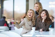 Amigos de risa en la tienda del cofee Fotografía de archivo libre de regalías