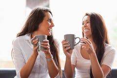 Amigos de risa que comen un café Fotos de archivo libres de regalías