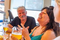 Amigos de risa que gozan de los vidrios de cerveza micro del brebaje en la barra imagen de archivo libre de regalías