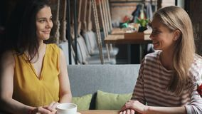 Amigos de señoras jovenes alegres que hablan riéndose de la tabla en el café que disfruta de ocio metrajes