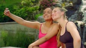 Amigos de Selfie al aire libre Muchachas alegres que se divierten en el parque que toma el selfie almacen de metraje de vídeo