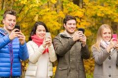 Amigos de sorriso com os smartphones no parque da cidade Imagem de Stock Royalty Free