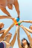 Amigos de sorriso no círculo na praia do verão Fotografia de Stock Royalty Free