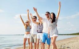 Amigos de sorriso que andam na praia e nas mãos de ondulação Imagem de Stock